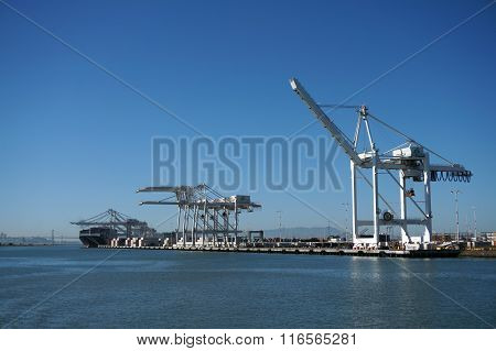 Shipping Cargo Boats Line Up In Harbor Under Giants Unloading Cranes In Oakland Harbor