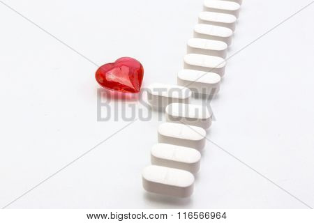 Aligned White Pills, A Transparent Red Heart