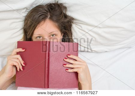 Sleepy Girl Laying In A Bed With A Book