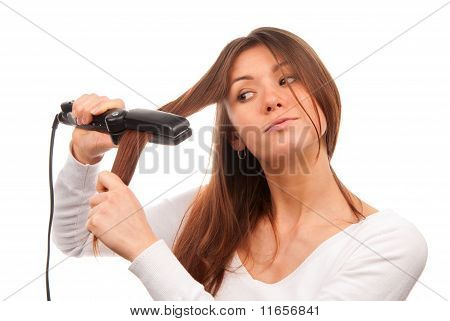 Woman Using Hair Straighteners For Stylish Hairstyle