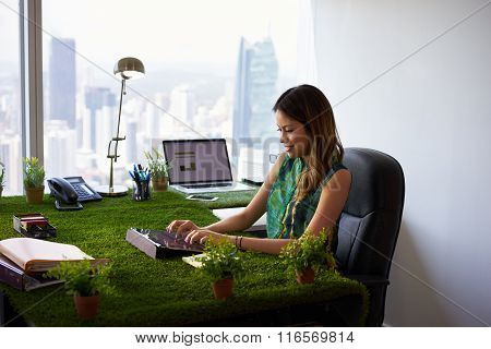 Environmentalist Woman Types Email With Tablet On Office Desk