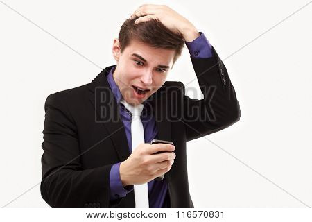 Young Businessman Amazedly.looking At The Phone Holding On To The Head