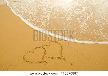 Drawing a heart on the sand beach and wave