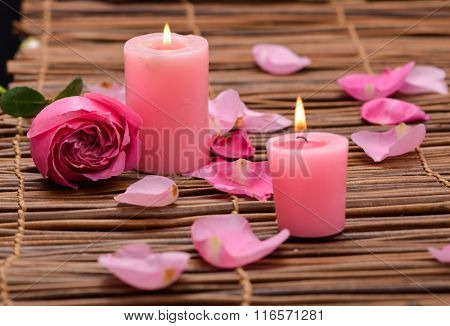 rose with candle and petals on mat