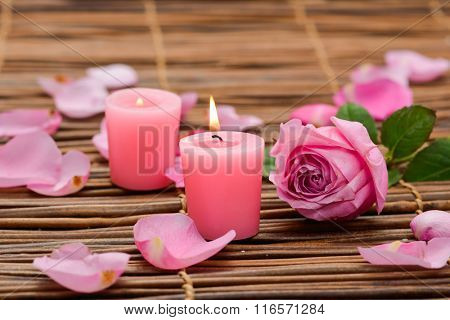 Two Candles and rose Petals on mat