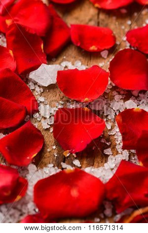 Red roses petals with salt on old wooden board