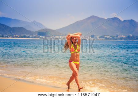 Blonde Girl In Bikini Poses Crosses Arms Over Head On Beach