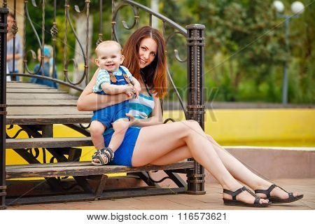 Mother And Daughter Sitting On Steps Of Bridge.