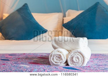 White Bath Towel Rolled Up On A Bed In Hotel Room.