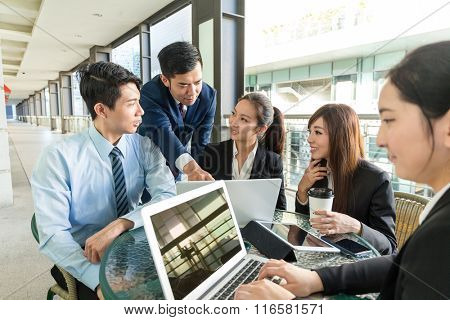 Group of business people discuss about project at outdoor coffee shop