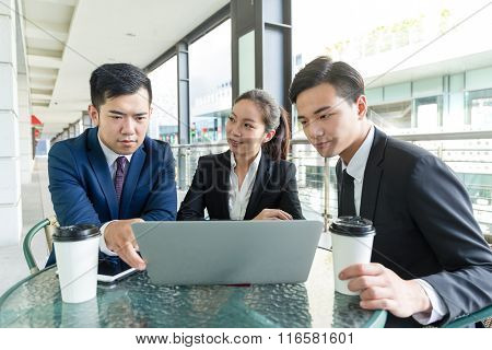 Group of asian business people discuss something on laptop computer