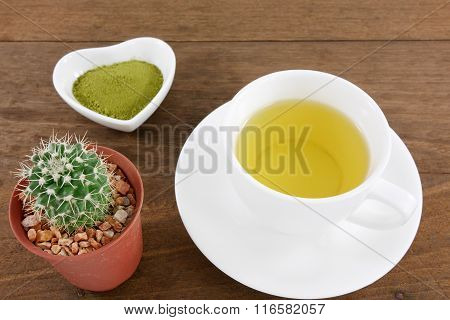 The Japanese matcha green tea powder on ceramic heart shaped bowl and cup of hot green tea