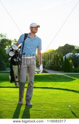 Young man with a golf bag outdoors