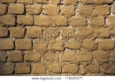 Old brick ochre painted wall. Background texture.