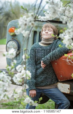 Dreaming teenager with closed eyes wearing knitted melange sweater outdoors with vintage russet suit