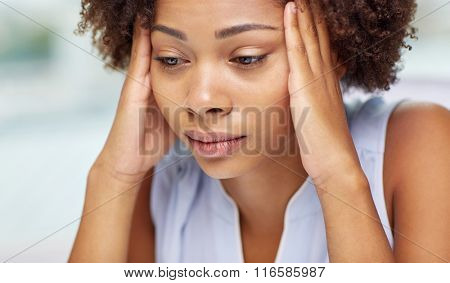 close up of african young woman touching her head