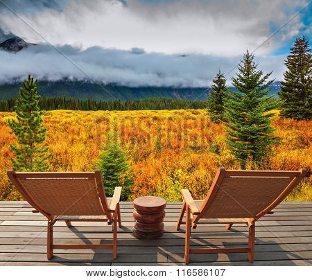The lush  autumn in Rocky Mountains of Canada. On the wooden platform there are two wicker deck chairs