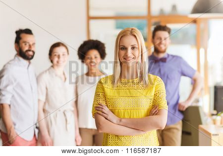 happy young woman over creative team in office