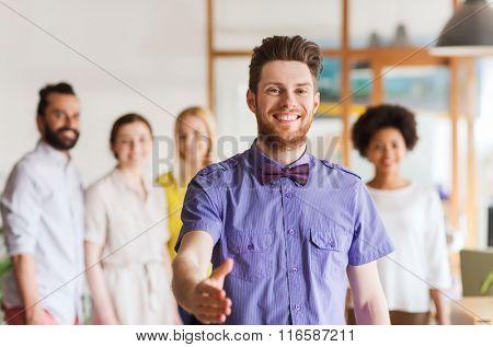 happy man making handshake over office team