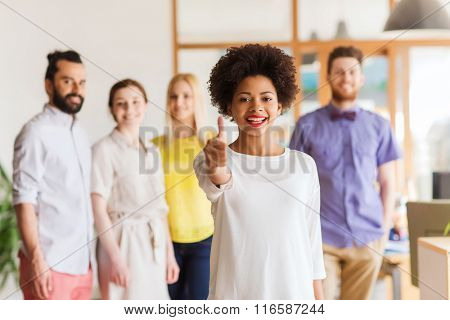 woman showing thumbs up over creative office team