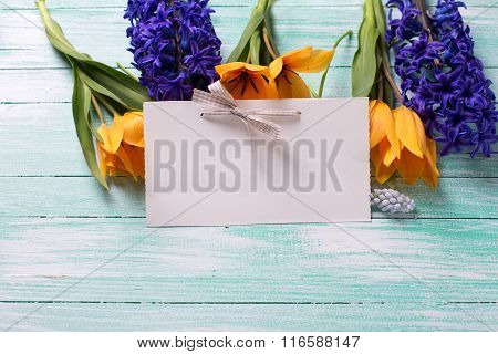 Yellow Tulips, Blue Hyacinths  Flowers  And Empty Tag On Turquoise  Painted Wooden Planks.