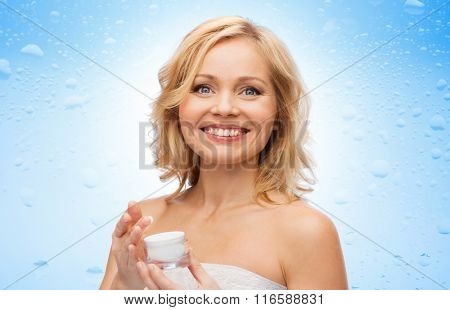 happy middle aged woman with moisturizing cream