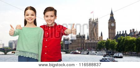 happy boy and girl showing thumbs up over london