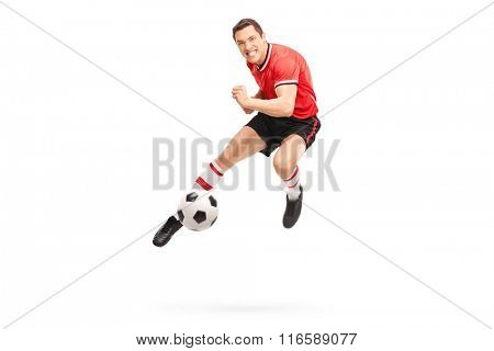 Studio shot of a young football player kicking a ball shot in mid-air isolated on white background