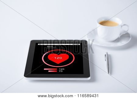 tablet pc with heart rate icon and cup of coffee