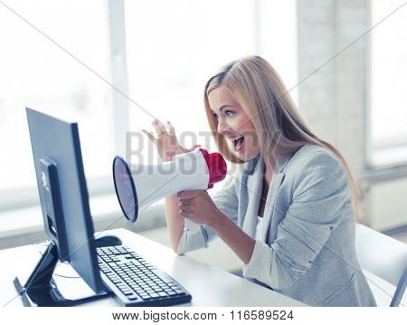 crazy businesswoman shouting in megaphone