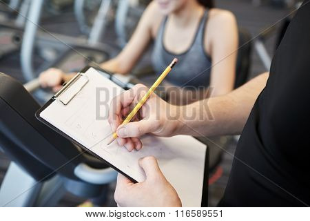close up of trainer hands with clipboard in gym