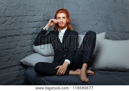 On The Sofa Sits Cross-legged Guy.