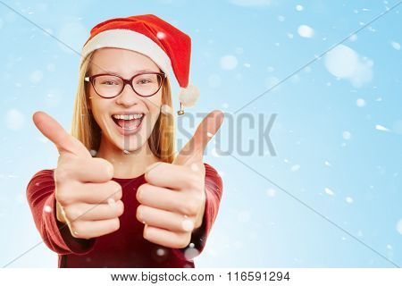 Smiling young blond woman with thumbs up in the snow at christmas