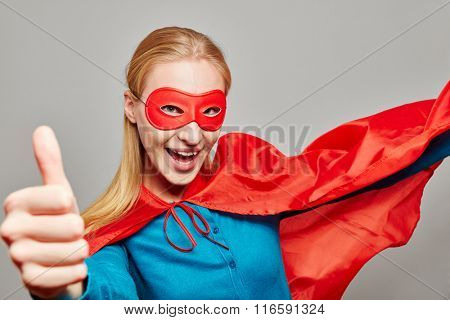 Smiling woman dressed up as a superhero holding her thumb up