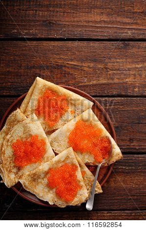 Pancakes with red caviar at home, top view