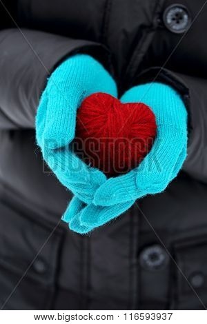 hands in knitted holding red heart