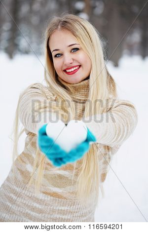 blonde woman holds a heart