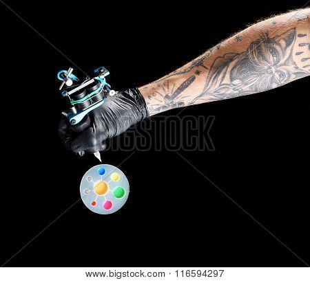 Tattooist hand in medical glove with tattoo machine and colourful inks on black background