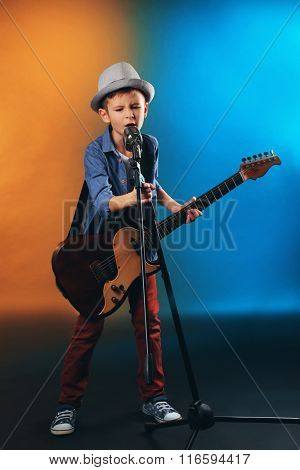 Little boy playing guitar and singing with microphone on a dark lighted background