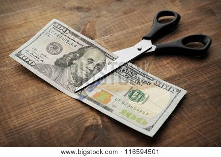 Scissors cuts dollar banknote on wooden background