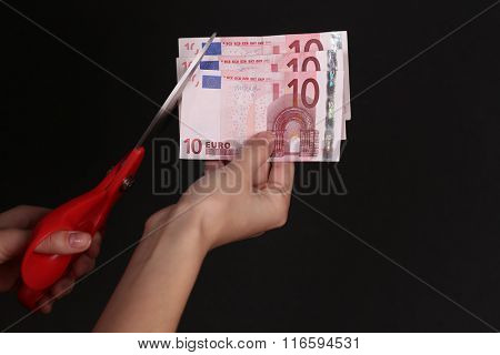 Hands with scissors cutting Euro banknotes, on black background