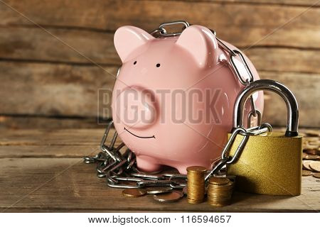 Piggy bank and chains on wooden background