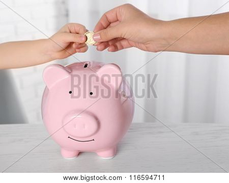 Savings concept. Hand putting coin in the piggy bank, close up