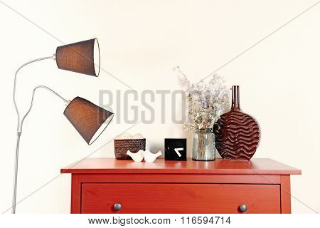 Room interior with red wooden commode, lamp and vase on light wall background