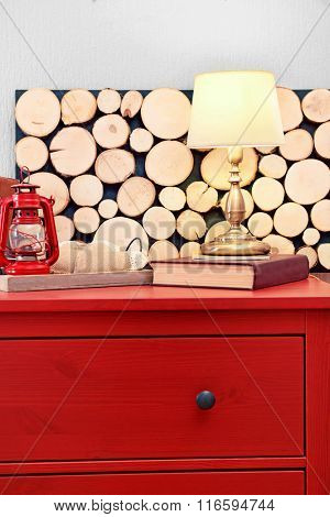 Room interior with red wooden commode, lamp and lantern on light wall background