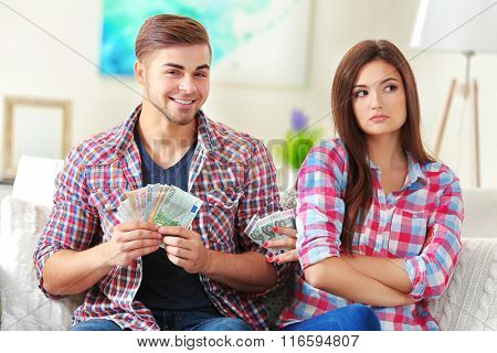Happy couple counting money from the moneybox