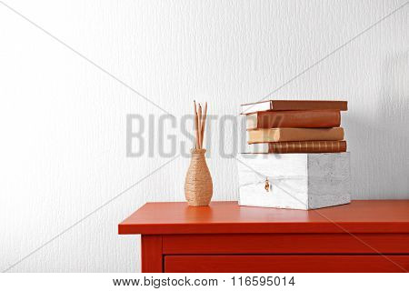 Room interior with red wooden commode and books on light wall background