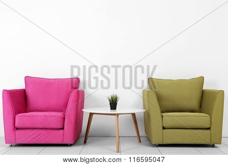 Living room interior with pink, green armchairs, white table and plant on white wall background