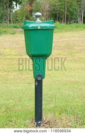 The Golf Ball Washer With Green Golf Course Background.
