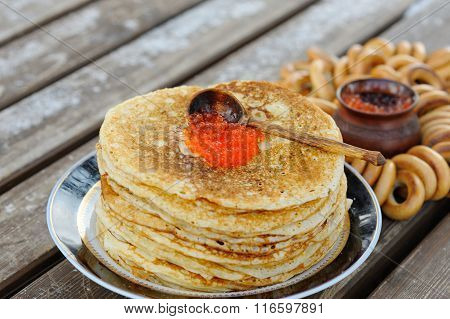 A Stack Of Delicious, Pancakes With Red Caviar Laid Out On The Plate. Next To The Pancakes Are The B